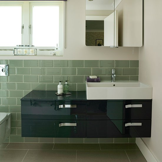 Awesome A Curved Metal Vanity Mirror Paired With A White Bathroom Sconce Is Lit Over A White Quartz Countertop With Chrome Faucet White And Gray Mosaic Floor Tiles Lead To A Stunning Green Gray Washstand Donning Polished Nickel Cup Pulls And A