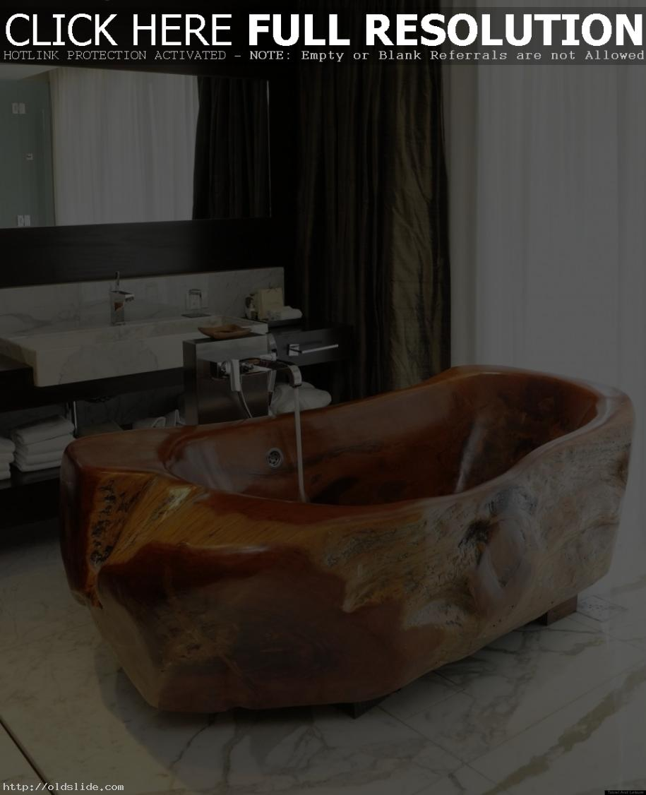 Contemporary-bathroom-concept-with-natural-stone-bathtub-and-amazing-modern-faucet-on-seamless-white-ceramic-tiles-floor