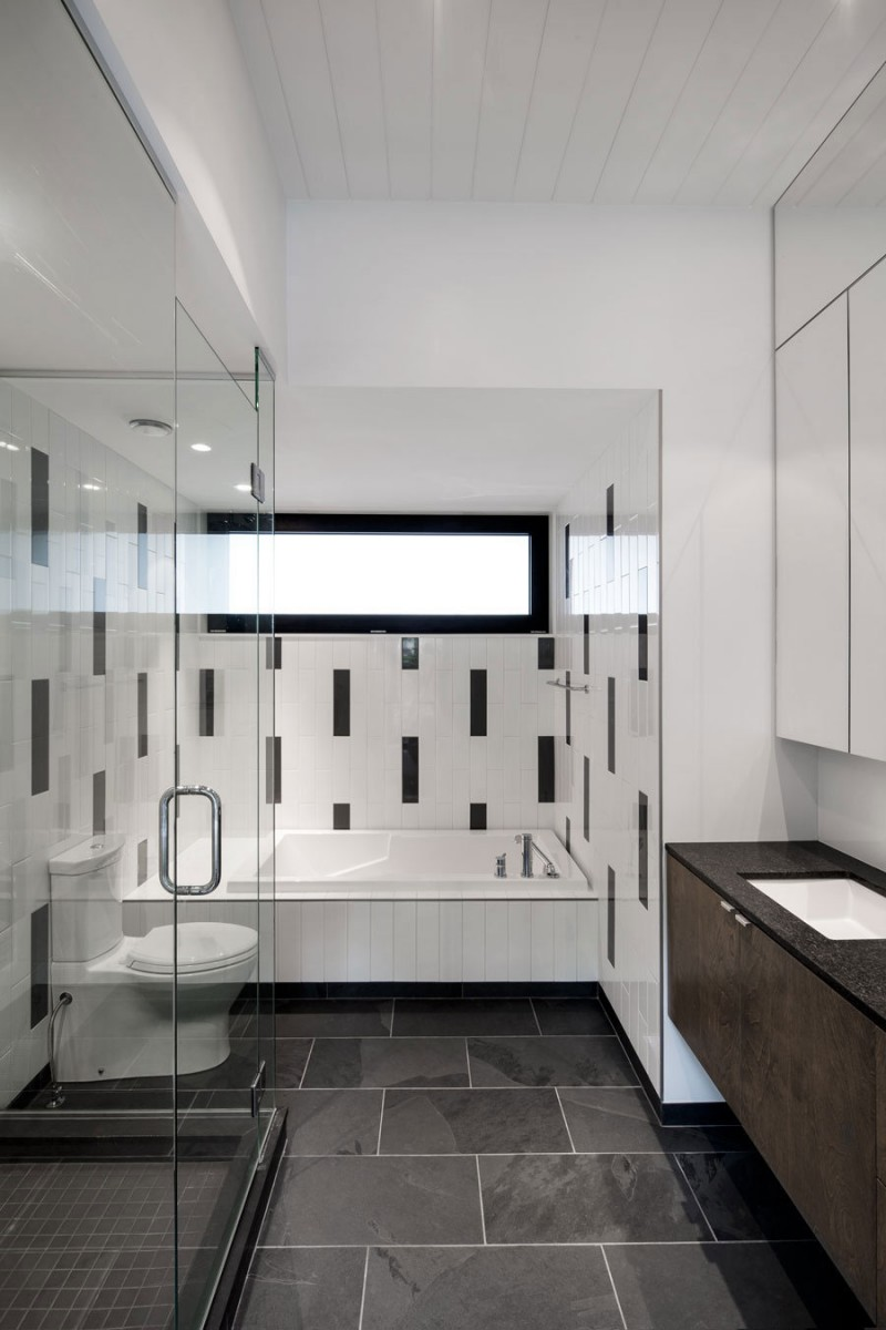 bathroom-interior-elegant-white-tiles-for-tub-surround-in-the-contempo-bathroom-design-glass-stall-shower-white-toilet-white-square-bathtub-brown-vanity-black-countertop-black-natural-stone-floor-c