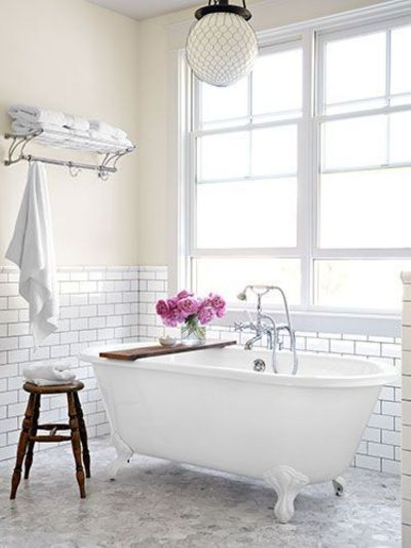 carrara-marble-floor-pairs-with-subway-tile-bathroom-walls-in-white-bathroom-with-clawfoot-tub-with-faucet