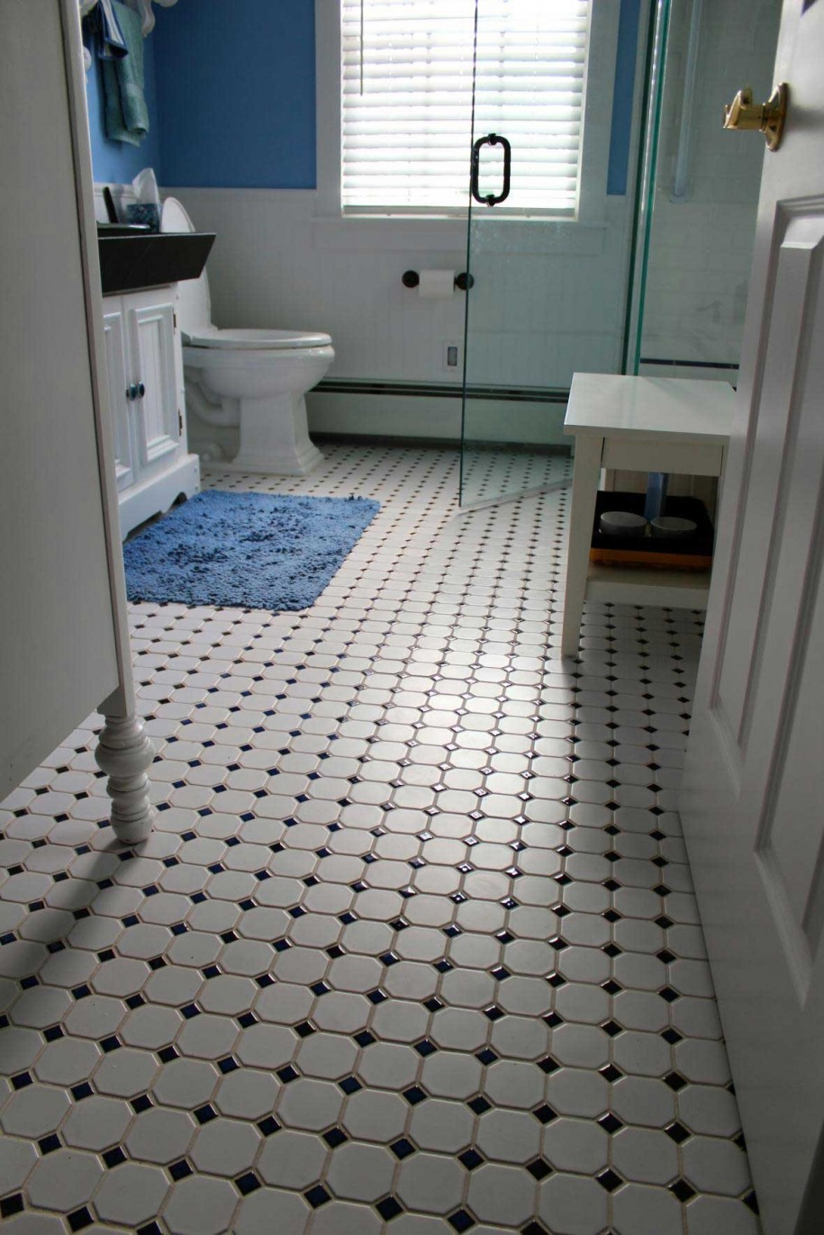 astonishing-bathroom-design-featuring-glass-shower-room-and-white-toilet-also-painted-white-bath-vanity-plus-white-bench-with-vintage-tiles-floor-pattern-and-blue-mattress-decor-vintage-bathroom-tile