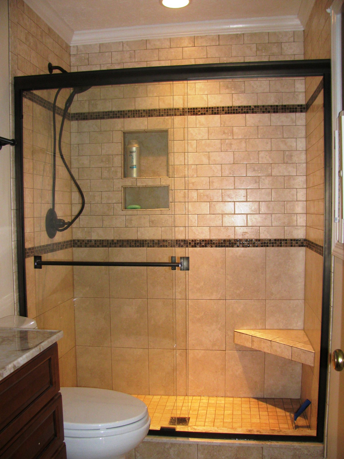 ceramic-subway-bathroom-wall-tile-shower-head-glass-cabin-partition-walls-with-black-frame-corner-bath-seat-brown-small-vanity-the-latest-styles-and-designs-of-bathroom-showrooms-1200x1600