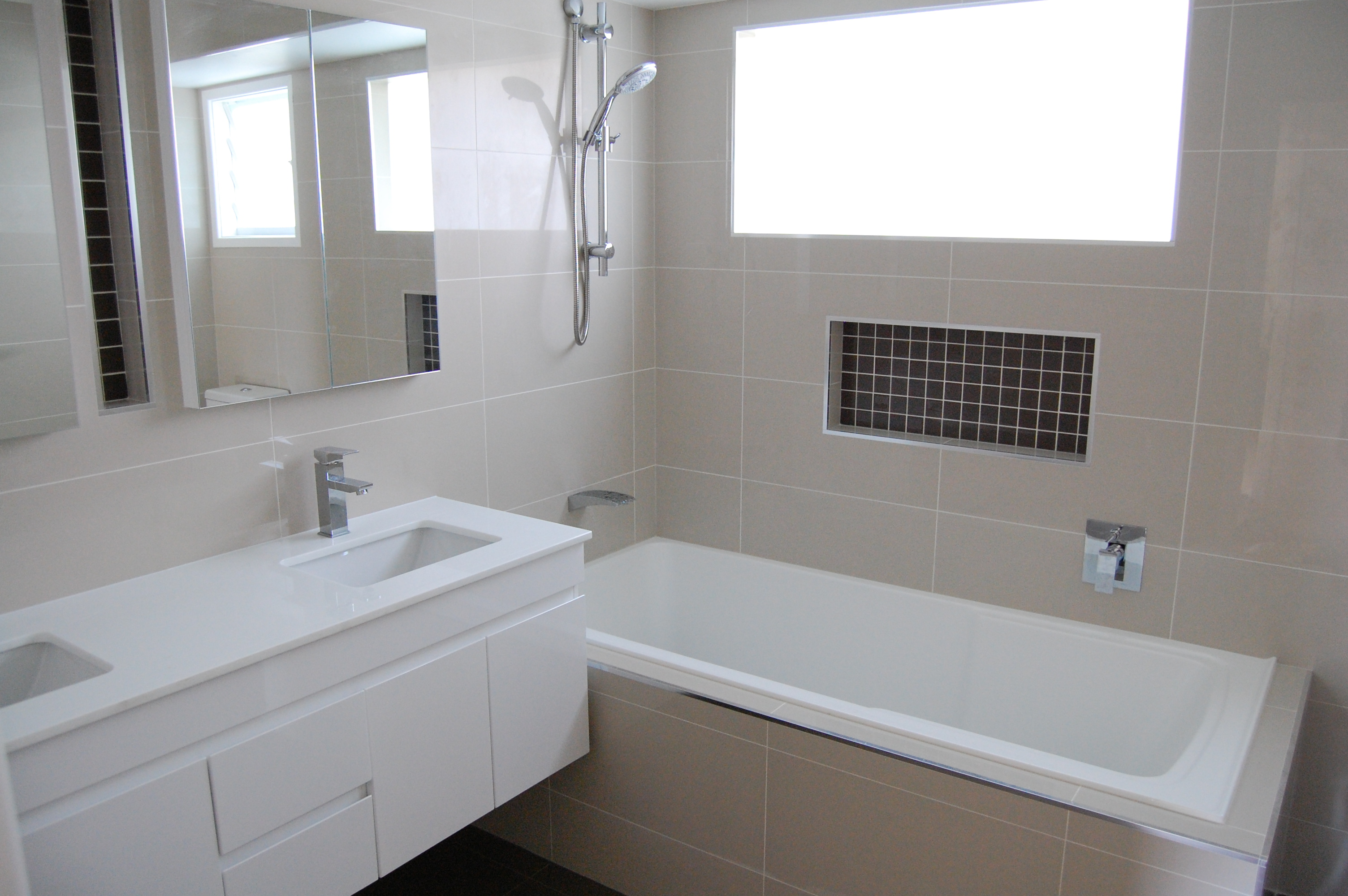 Neutral-Bathroom-With-Ceramic-Tile-Floor-With-Wash-Hasn-Double-Small-Mirror-With-White-Bathtub